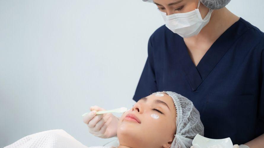 Dokter kulit kelamin yang bagus melakukan perawatan di wajah pasien untuk mengatasi jerawat